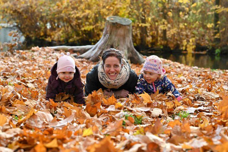 rodinne fotenie s detmi na jesen v Stupave, rodina lezi na zemi na farebnych listoch v parku