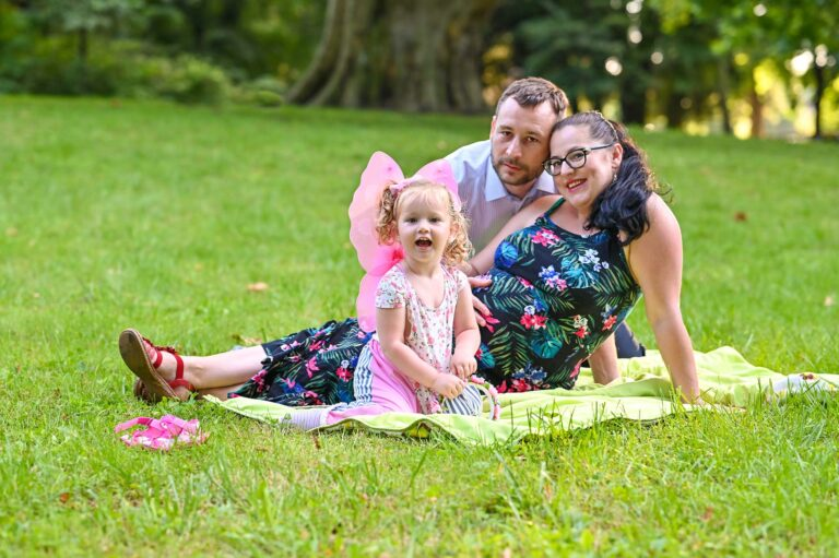 tehotenske fotenie v parku v Stupave, rodina sedi na deke na trave